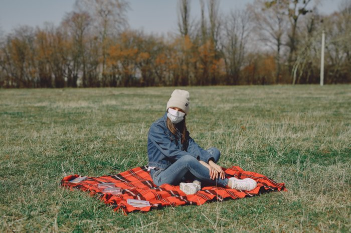 young-girl-in-face-mask-resting-on-plaid-in-park-4127442
